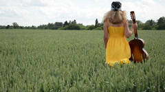 Musician with guitar in hand walks dreamily corn fields Stock Footage