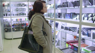 Stock Video Footage of Woman looking for new gadget in electronics store