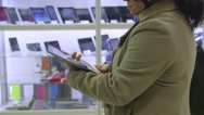 Stock Video Footage of Customer testing new digital tablet at electronics store