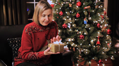 Mature Caucasian Woman Receives A Christmas Holiday Gift With Xmas Tree Stock Footage
