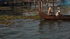 Men in straw hats rowing wooden fishing canoe in river in Kochi, India- tracking Stock Footage