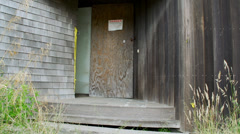 Boarded up front door with danger notice posted Stock Footage