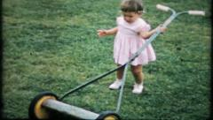770 - little girl is going to help cut the grass - vintage film home movie Stock Footage