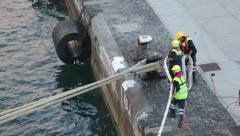 Shore crew put ships moorings lines over harbour bollard Stock Footage
