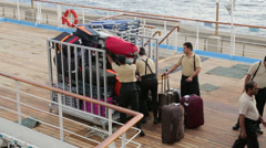 Men loading baggage crate for offloading from cruise ship Stock Footage