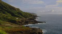 OAHU – HAWAII – GREEN COASTAL HILLS BY THE OCEAN (ZOOM IN) - stock footage