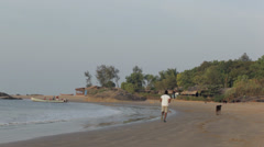 Panning- beach life in India- man jogging, cow+ fisherman pushes boat out to sea Stock Footage