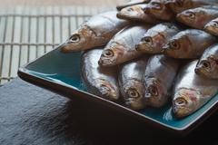 Fresh tasty raw sprats on serving dish Stock Photos
