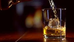 Pouring a scotch whiskey on the rocks Stock Footage