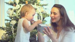 Mother and Baby with Gift near the Christmas Tree Stock Footage