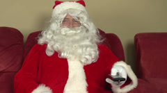 Santa Claus channel surfing on couch pan - stock footage