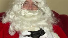 Santa Claus playing video games on couch Stock Footage