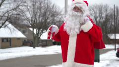 Santa walking by with bag of gifts on sidewalk Stock Footage