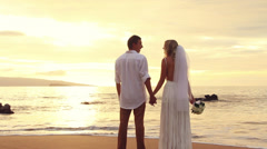 Newly married couple kissing on tropical beach at sunset Stock Footage