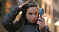 Woman on the street uses a mirror to comb , light and decoration in background Stock Footage