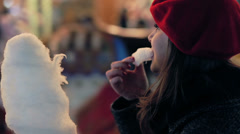 Happy woman eats cotton candy and looks carousel horse , marry-go-round Stock Footage