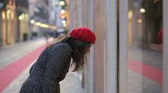 Beautiful girl is looking in a shop window in a prestigious street of Rome Stock Footage