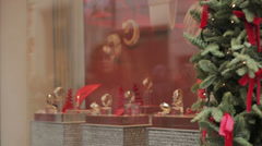 Woman looks at a shop window with exposed watches to make a Christmas gift Stock Footage