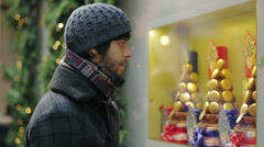 Young man looks in the shop window of a candy store - during christmas time Stock Footage