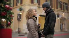 Young loving couple embracing each other in the street during Christmas period Stock Footage