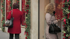 Beautiful woman looks at a shop window with exposed watch at Christmas time Stock Footage
