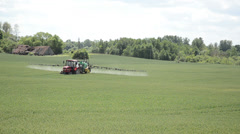 Tractor fertilize green crop field near village houses in summer Stock Footage