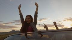 Teen Stands, Raises Her Arms & Yells In A Convertible To Celebrate w/Friends  Stock Footage