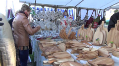 Women buy wooden tools from the craftsman at the market stall Stock Footage