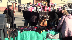 Zoom in vendor woman sell gloves and people size them in market Stock Footage