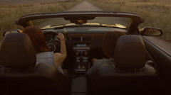 Young Women Going Down A Desert Road In A Convertible Stock Footage