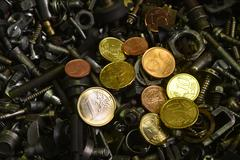 shine of coin in a sea of old screws - stock photo