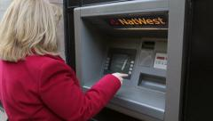 Woman draws sterling money from atm machine Stock Footage