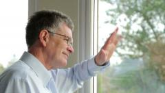 Middle aged man looks out of the window, smiles and waves at someone - stock footage