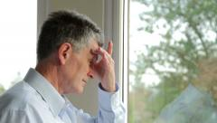 close up, serious, unhappy middle aged man looks out of the window - stock footage