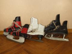 three pairs of old skates lying on the parquet floor - stock photo