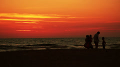 Silhouette of family on the beach at sunset Stock Footage