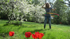 Woman turn hula hoop ring on waist in beautiful spring garden Stock Footage