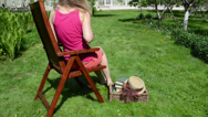Stock Video Footage of Botanist woman on wooden chair check dried leaves in old book