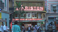 Ariston theatre Sanremo San Remo building neon sign people walking sidewalk day Stock Footage