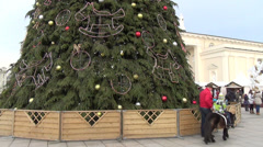 Child rides with keeper along fence at christmas decoration tree Stock Footage