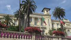 Municipal Casino San Remo Sanremo building facade Italy palm tree blue sky town Stock Footage