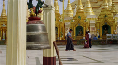 Monks and devotees walk past large bell at Shwedagon Pagoda Stock Footage