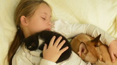 Little girl sleeping hugging kitten and puppy Stock Footage
