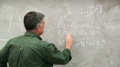 Man writing scientific equations on a chalk board Stock Footage