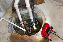 Repairing a sump pump in a basement Stock Photos