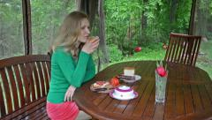 Happy woman eat breakfast and drink juice in garden bower house Stock Footage