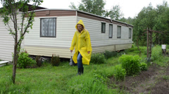 Woman with waterproof raincoat walk in near small movable house Stock Footage