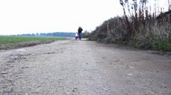 Mother with her little daughter walking along a country road. - stock footage