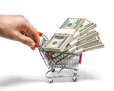 Käsi työntää ostoskärryt täynnä kasana dollarin seteleitä - stock photo