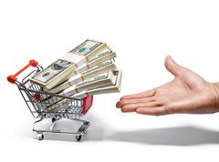 Hand tarjoaa ostoskorin täynnä rahaa pinot - stock photo